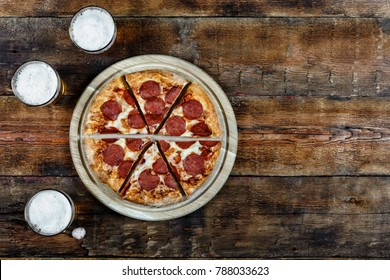 Pepperoni pizza and beer pills on a wooden table in the pub, top view, Rustic  style.
