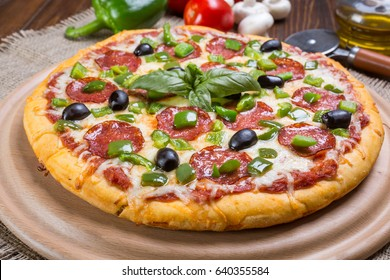 Pepperoni Pizza with Black Olives and Green Pepper on a cutting board