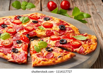 Pepperoni pizza with cherries tomatoes an olives on wooden table
