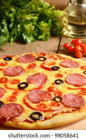 Pepperoni pizza with cherry and paprika on the kitchen table