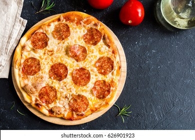 Pepperoni Pizza - Fresh homemade pizza with pepperoni, cheese and tomato sauce on rustic black stone background wirh copy space.