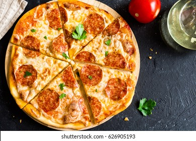 Pepperoni Pizza - Fresh homemade pizza with pepperoni, cheese and tomato sauce on rustic black stone background with copy space.
