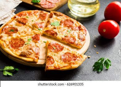 Pepperoni Pizza with ingredients - Fresh homemade pizza with pepperoni, cheese and tomato sauce and ingredients on rustic black stone background with copy space.
