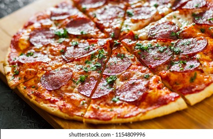 Pepperoni Pizza with Mozzarella cheese, salami, Tomatoes, pepper, Spices and Fresh Basil. Italian pizza
