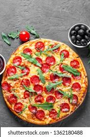 Pepperoni Pizza with Mozzarella cheese, salami, Tomatoes, pepper, Spices and Fresh arugula. Italian pizza on Dark grey black slate background