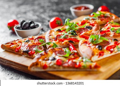 Pepperoni Pizza with Mozzarella cheese, salami, Tomatoes, olive, pepper, Spices and Fresh arugula. Italian pizza on dark background