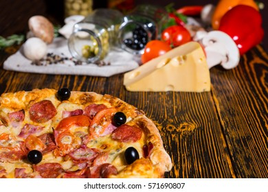 Pepperoni pizza with olives, near lie tomatoes, cheese, mushrooms and other vegetables on napkin on wooden table