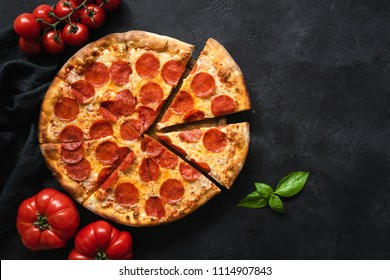 Pepperoni pizza on black concrete background. Top view with copy space. Tasty sliced pepperoni pizza