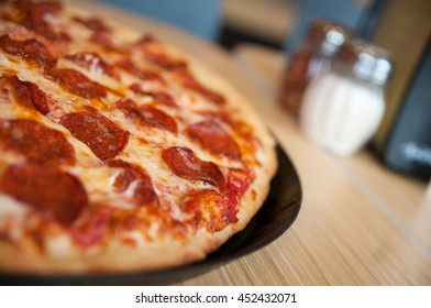 Pepperoni pizza on a restaraunt table with shallow depth of field