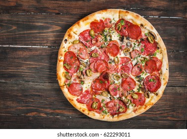 Pepperoni pizza on rustic, vintage style wood background. Top view