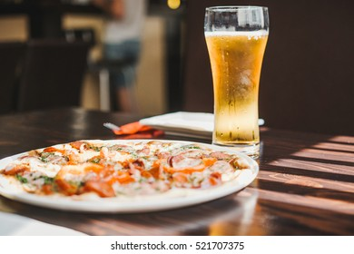 Pepperoni pizza on a table with beer