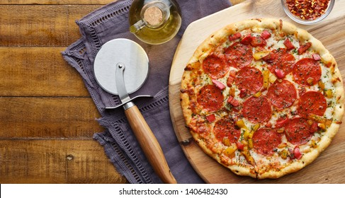 pepperoni pizza on wooden serving tray with cutter flat lay composition panorama