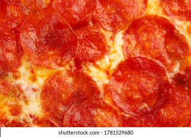pepperoni pizza texture closeup with basil top view. pizza background