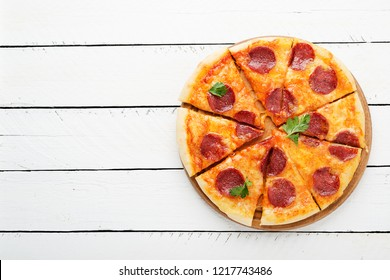 Pepperoni pizza, tomatoes and parsley. Tasty pepperoni pizza on white wooden background. Overhead view of italian pizza.