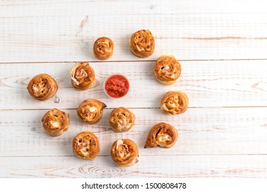 Pepperoni Rolls with sauce in the form of a spiral on a white wooden background. Tasty italian fast food
