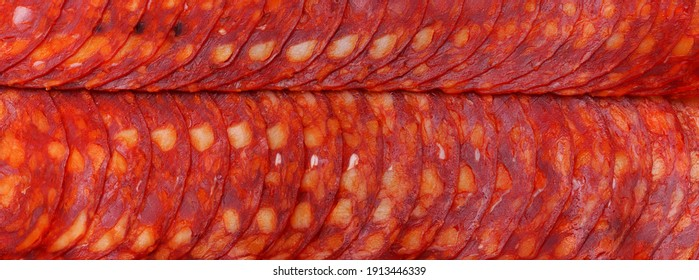 Pepperoni. Pepperoni sausage slices. Piquant,spicy, durable sausages.Cured meat products. Food background. Close up.Panoramic macro image. hi-res banner.