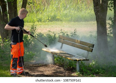 Perach Germany-,May 9,2018: A city  worker  cleans a park bench with a high pressure hose