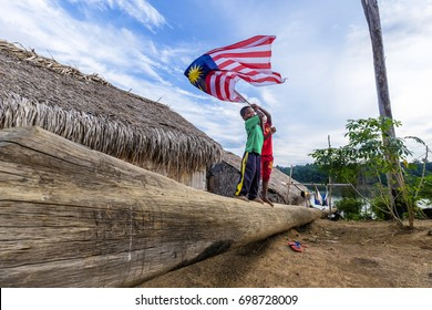 Perak , Malaysia - 18 August 2017 - Aboriginal kids show a spirit of independence of Malaysia by flying their national flag in rural area in deep rain forest Royal Belum Malaysia.