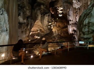 PERAK, MALAYSIA - APRIL 02, 2019: Two tourist sees a unique granic stone found in the Tempurung cave in Gopeng, Perak Malaysia.