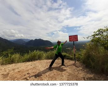 PERAK, MALAYSIA -Mach 14, 2019: A hiker made an action at the top of Batu Putih Hill as high as 310 meters above sea level located in Perak Malaysia.