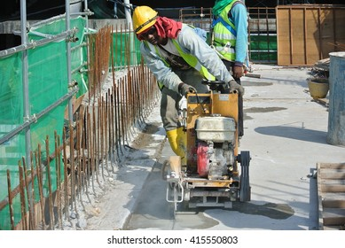 PERAK, MALAYSIA -MARCH 29, 2016: Construction Workers cutting concrete slab or asphalt using saw blade at the construction site.
