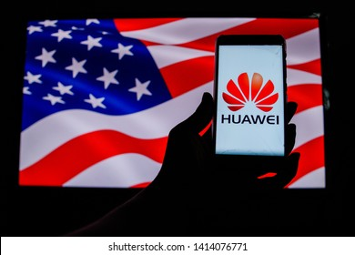 PERAK, MALAYSIA - MAY 24, 2019: A man holds an android-smartphone that shows the Huawei logo in front of the USA flag. Google is restricting Huawei's access to its Android system.