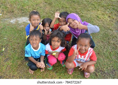 PERAK, MALAYSIA - OCTOBER 7, 2017 : A group of aborigine children play together at a field near their village.