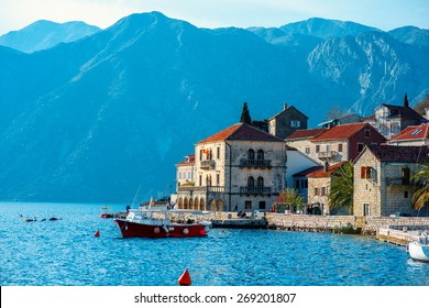 Perast city in Kotor bay on the sunset with beautiful mountains and boat floating in Montenegro