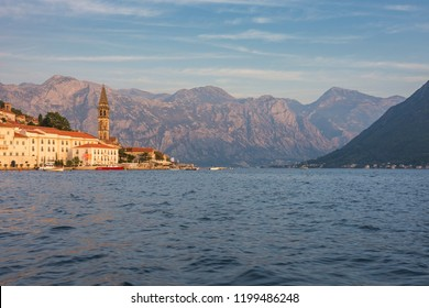 Perast, Montenegro - 09/22/2018: View of ancient town of Perast, lit up by the sunset.  The bell tower of the church of St. Nicholas in the distance. Bay of Kotor at early autumn. Cityscape
