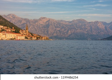 Perast, Montenegro - 09/22/2018: View of ancient town Perast, lit up by the sunset.  The bell tower of the church of St. Nicholas in the distance. Bay of Kotor at early autumn. Cityscape