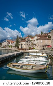 Perast, Montenegro - April 2018 : Row of anchored fishing boats on the shore in the beautiful Perast town in the Kotor Bay