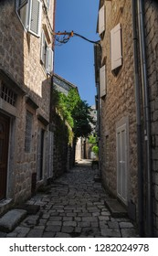 Perast/ Montenegro Aug 2016: Narrow street of authentic old town Perast, Montenegro. We see old houses and a narrow street with a stone wall
