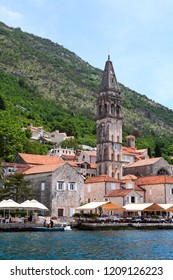 PERAST, MONTENEGRO - CIRCA JUN, 2016: View from sea at Perast cityscape with bank, ancient houses, fort tower and St Nicholas church with belltower. The Adriatic sea, Kotor gulf