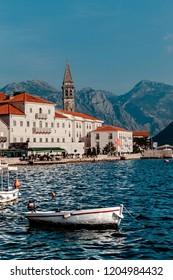PERAST, MONTENEGRO. Cityscape of Perast on coast of Boka Kotor bay. Beautiful mediterranean landscape.Unknown people walk along promenade of small popular resort town of Perast.