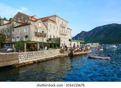 PERAST, MONTENEGRO - SEPTEMBER 13, 2017: Unknown people rest in cafe near Smekja Palace on promenade of popular resort town of Perast, Montenegro
