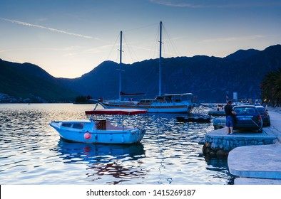 PERAST, MONTENEGRO - SEPTEMBER 13, 2017: Boats at waterfront of resort town of Perast against backdrop of mountains, evening view. Unknown people are on seafront