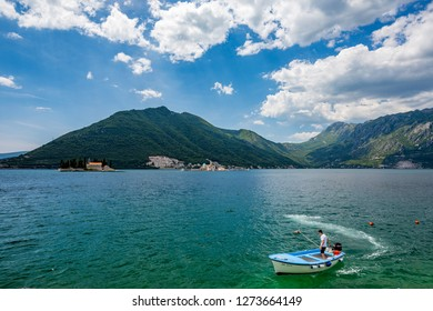 PERAST, MONTENGRO - MAY 16, 2017: Young man rules small wooden boat in the blue waters of Boka Kotor bay with the two churches Our Lady of the Rock and St.George Island in Perast in background