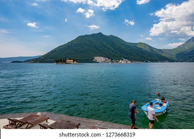 PERAST, MONTENGRO - MAY 16, 2017: Two young men moor small wooden boat in the blue waters of Boka Kotor bay with the two churches Our Lady of the Rock and St.George Island in Perast in background