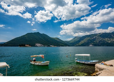 PERAST, MONTENGRO - MAY 16, 2017: Young men servicing small wooden boat in Boka Kotor bay with the two churches Our Lady of the Rock and St.George Island in Perast in background and sunbathing girl