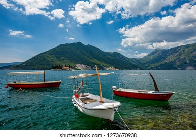 PERAST, MONTENGRO - MAY 16, 2017: Three small tourist wooden boats moored in Boka Kotor bay with the two churches Our Lady of the Rock and St.George Island in Perast in background, sunny spring day