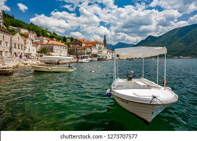 PERAST, MONTENGRO - MAY 16, 2017: Wooden white boats used to get tourists to the two churches Our Lady of the Rock and St.George Island float in Perast. Boka Kotor bay sunny spring day, crystal water