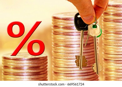 The percent symbol and keys in the background the columns of coins . The concept of mortgage lending .