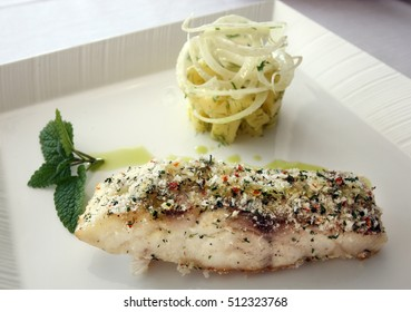 Perch fish (Turkish: Levrek) with potato salad on the dinner plate.