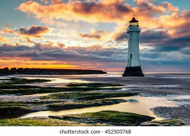 Perch Rock Lighthouse with rock pools in the foreground at New Brighton, Merseyside. Taken at sunset.
