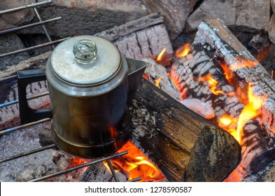 Percolating coffee on a campfire with glowing flames.
