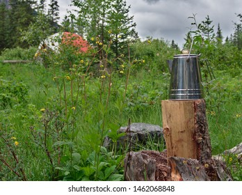 Percolator coffee pot in the foreground and blurred background with a camping tent