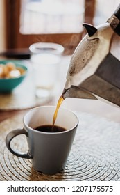 Percolator pouring cup of coffee at cozy breakfast table