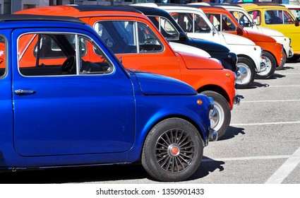 Percoto,Italy. March 24 2019. A row of colorful Fiat 500s  in a roadside parking lot, waiting to participate in an auto gathering later