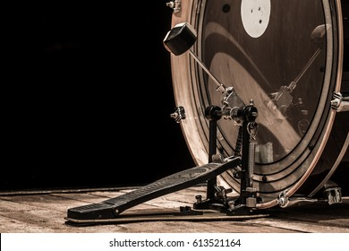 percussion instrument, bass drum with pedal on wooden boards with a black background, the music concept