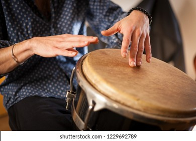 Percussion instrument being played concept. Represented by percussionists hands hitting a drum.